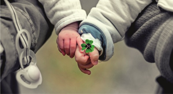 Zwei Kinderhänder mit Kleeblatt